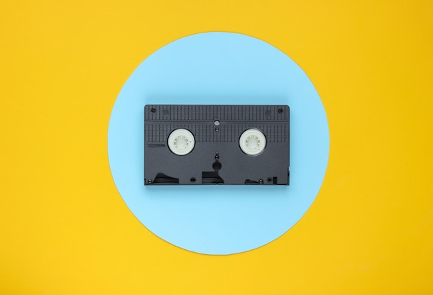Video cassette on yellow background with blue pastel circle. minimalistic retro concept.