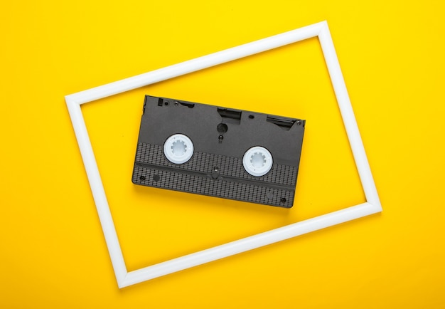 Video cassette on yellow surface with white frame