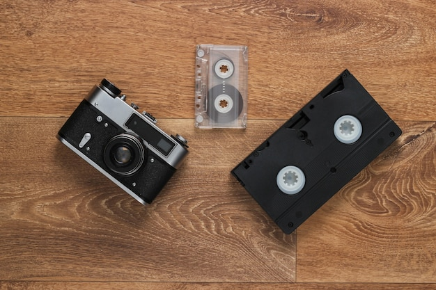 Video cassettes, audio cassette, old-fashioned film camera on the floor. retro media 80s. top view