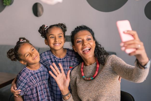 Видеочат. счастливая привлекательная стильная мама и две дочери в видеочате с отцом