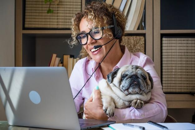 화상 회의 통화 젊은 성인 비즈니스 여자가 이야기하고 우정에서 함께 그녀의 미친 재미 퍼그 강아지와 함께 랩톱 컴퓨터에서 집에서 작동