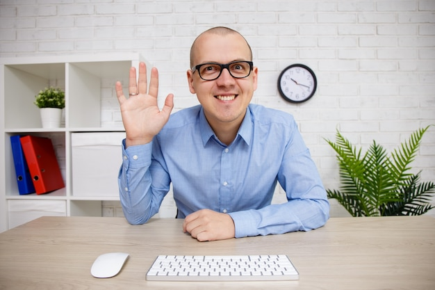 Video conference concept - young business man waving hello into webcam