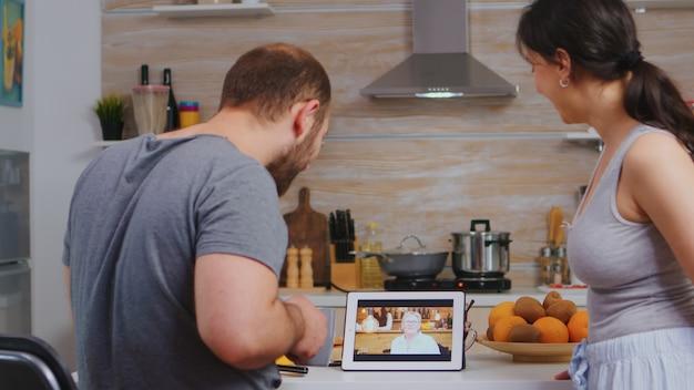 キッチンで美味しい朝食を楽しみながらおばあちゃんとのビデオ会議。親戚や友人とチャットするためにインターネットウェブオンライン技術を使用してパジャマの若いカップル