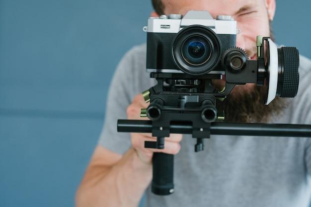 ビデオコンテンツの作成プロセス。カメラを通して見て、ブログや放送のために映像を撮影している男。