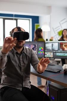 가상 현실 고글을 경험하는 비디오 편집자는 창의적인 작업 공간에 있는 포스트 프로덕션 소프트웨어에서 영화 몽타주를 표현합니다.
