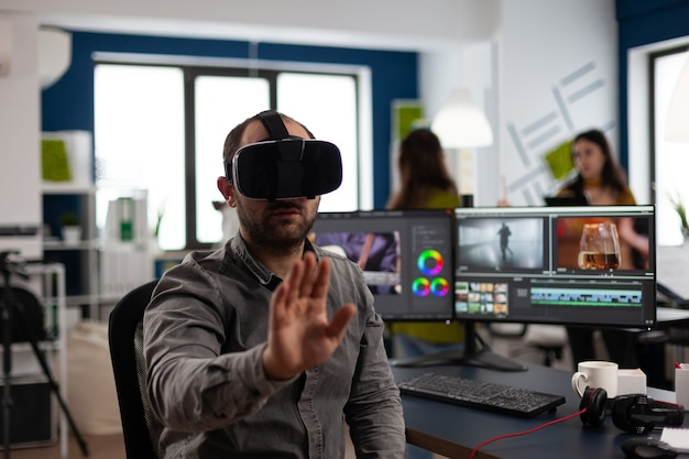Video editor experiencing virtual reality headset gesturing editing film montage