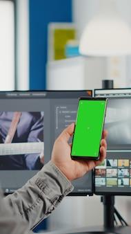 녹색 화면이 있는 스마트폰을 들고 화상 통화를 하는 비디오 편집기