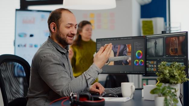 Видеоредактор разговаривает по видеозвонку, держит смартфон, редактирует фильм, сидя в стартап-креативном агентстве ...