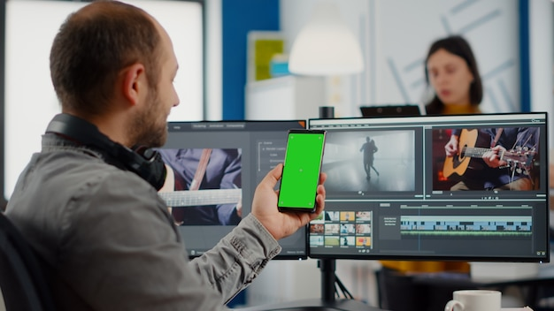Video editor talking on video call holding smartphone with green screen