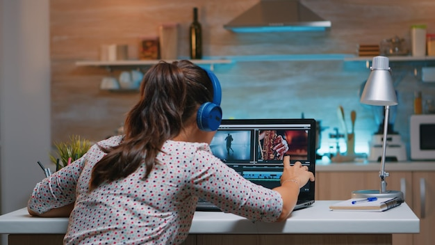 ヘッドセットを着用し、キッチンに座っているデジタルプロジェクトで自宅で作業しているビデオエディタ。真夜中に机の上に座っているプロのラップトップでオーディオフィルムモンタージュを編集するビデオグラファー