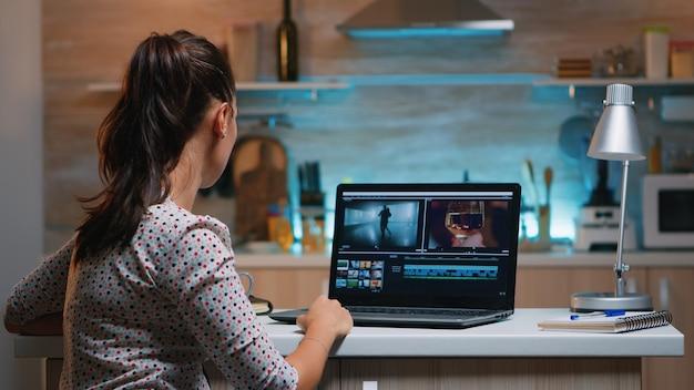 モダンなキッチンに座ってオーディオフィルムモンタージュを編集する新しいプロジェクトで夜に自宅で仕事をしているビデオエディタ。プロのラップトップ最新テクノロジーネットワークワイヤレスを使用するコンテンツクリエーター