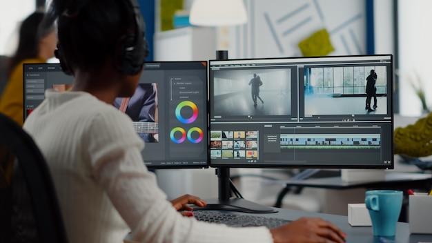 Видеоредактор, работающий с кадрами и звуком, монтаж нового проекта, монтаж фильма, монтаж, сидя в современном офисе агентства