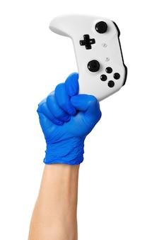 ゲーマーの手袋をはめた手でビデオゲームコンソールコントローラー。自宅で隔離中のゲーム、コロナウイルス