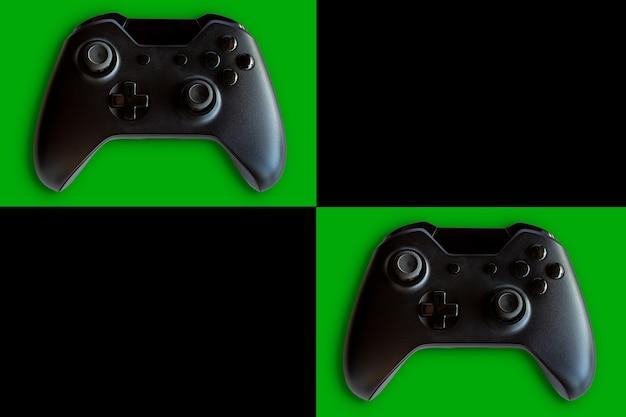 ビデオゲームコントローラーとゲームコントローラー。黒と緑の背景。セレクティブフォーカス。テキスト用のスペース。