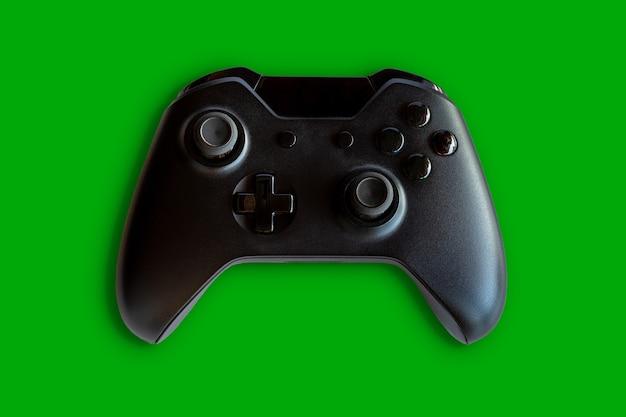 ビデオゲームコントローラーとゲームコントローラー。緑の背景。セレクティブフォーカス。