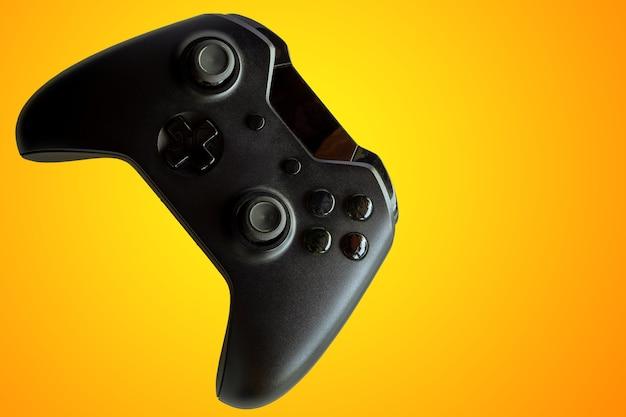 ビデオゲームコントローラーとゲームコントローラー。オレンジ色の背景。セレクティブフォーカス。テキスト用のスペース。