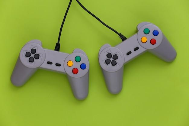 Геймпады для видеоигр. концепция игры два ретро джойстика на зеленом.