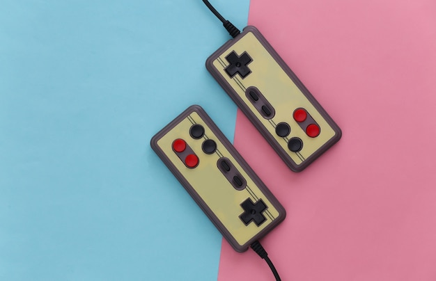 Геймпады для видеоигр. концепция игры два ретро джойстика на розовой голубой пастели.