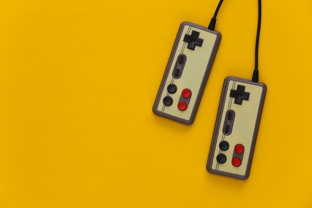 Геймпады для видеоигр. концепция игры два ретро джойстика на желтом.