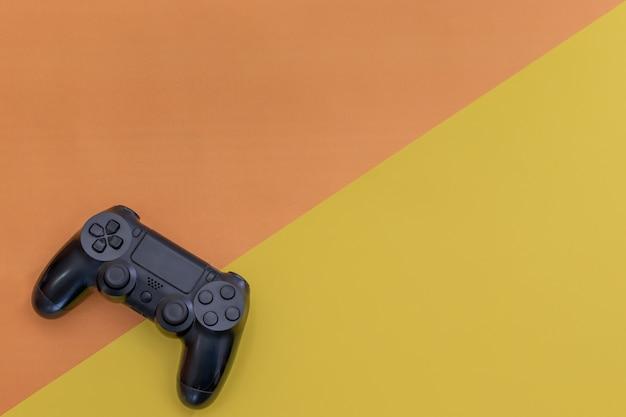 노란색 파란색 배경 상단 보기에 격리된 비디오 게임 검은색 게임 컨트롤러