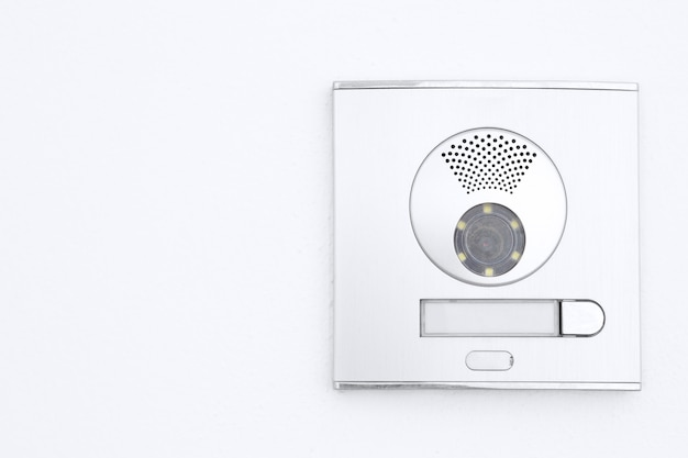 Video intercom display on white plastered wall with copy space