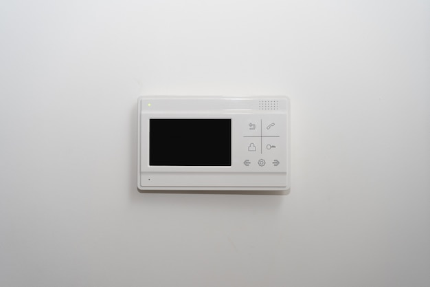 Video intercom on a white wall near the entrance door to the apartment