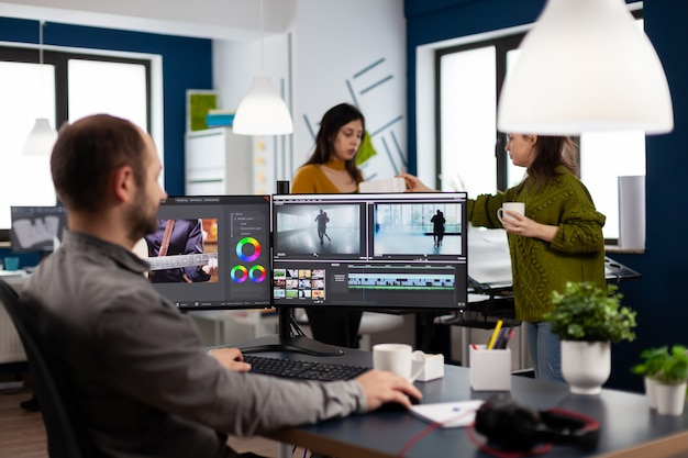 Video maker editing movie using post production software working in creative start up agency office with two monitors