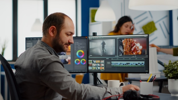 Video maker editing movie using post production software working in creative start up agency office ...