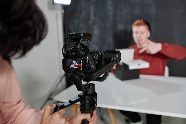 Video operator holding camera in front of vlogger opening black box while sitting by desk in studio