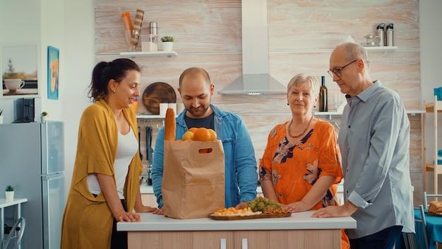 부엌에 앉아 카메라를 보며 웃고 있는 행복한 대가족의 비디오 초상화. 웹 캠을 보고 식료품과 함께 papper 가방 주위 식당에 있는 사람들