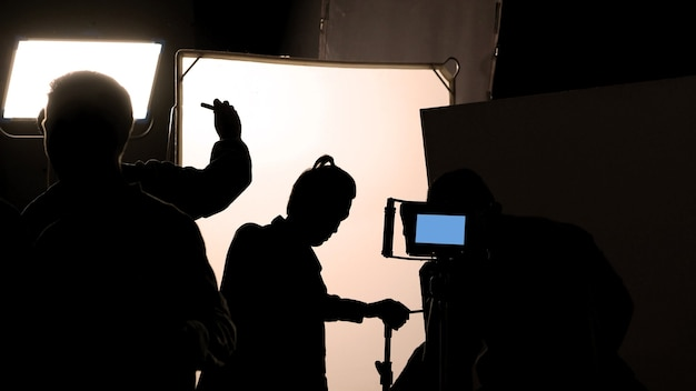 Video production behind the scenes which film crew team in silhouette shooting or recording tv movie