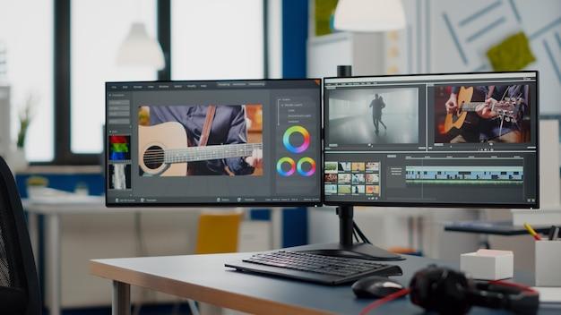 誰もいないビデオ制作スタジオと2台のディスプレイを備えたコンピューター