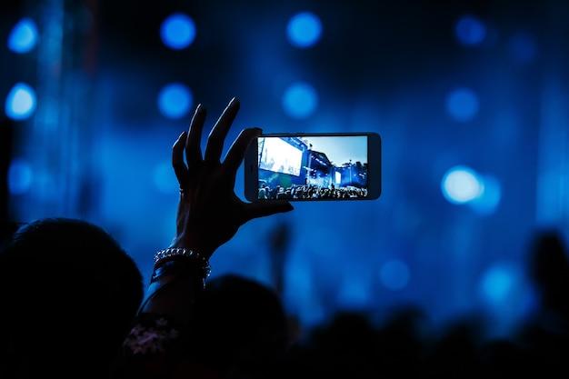 ビーチパーティーのスマートフォンでのコンサートのビデオ録画
