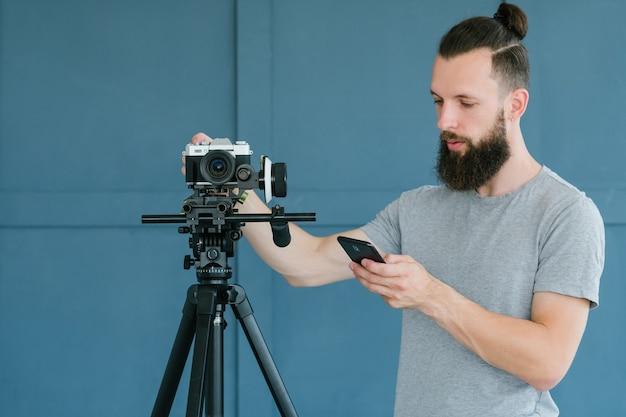 Концепция потокового видео и съемки. полезное оборудование для создания контента. оператор проверяет настройки камеры на своем телефоне.