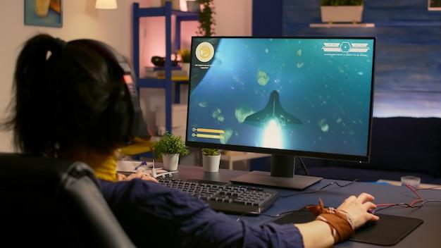 전문 헤드셋을 착용하는 동안 비디오 게임 플레이어가 우주 슈팅 경쟁에서 패배