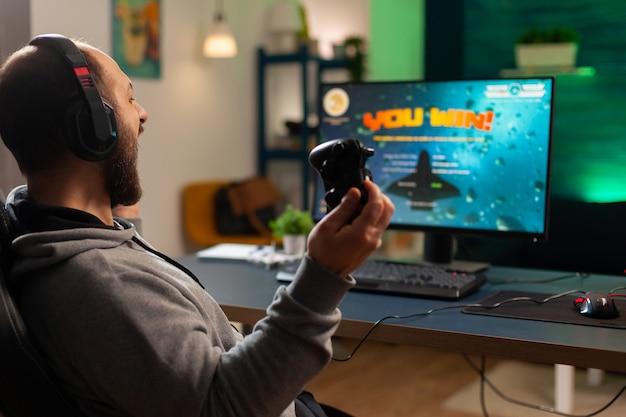 ヘッドセットを着用して宇宙シューティングゲームの競争に勝った後、手を上げるビデオゲームプレーヤー。ゲームルームから強力なコンピューターで新しいグラフィックスを使用してオンラインビデオゲームをプレイするプロゲーマー