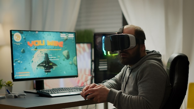 Videogame player with vr headset raising hands after winning space shooter competition. professional pro gamer playing online video games with new graphics on powerful computer from gaming room