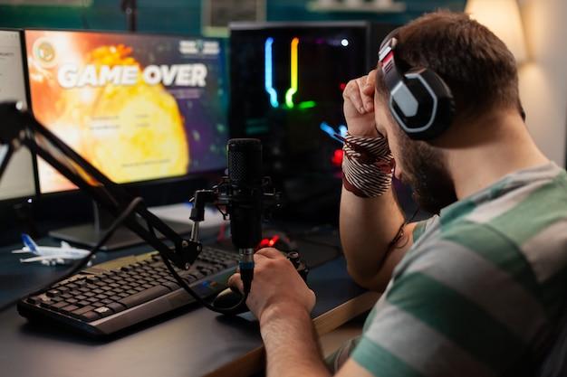 비디오 게임 스트리머는 전문 헤드셋을 착용하면서 비디오 게임 경쟁에서 지고 있습니다. 늦은 밤 게임 룸에서 온라인 토너먼트를 위해 최신 컨트롤러를 사용하여 게이머에게 패배
