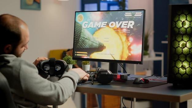 비디오게이머는 무선 컨트롤러와 강력한 컴퓨터에서 재생되는 vr 헤드셋을 사용하여 게임 의자에 앉아 그래픽 사이버스페이스 비디오 게임을 잃습니다. 슬픈 프로 사이버맨 스트리밍 온라인 챔피언십