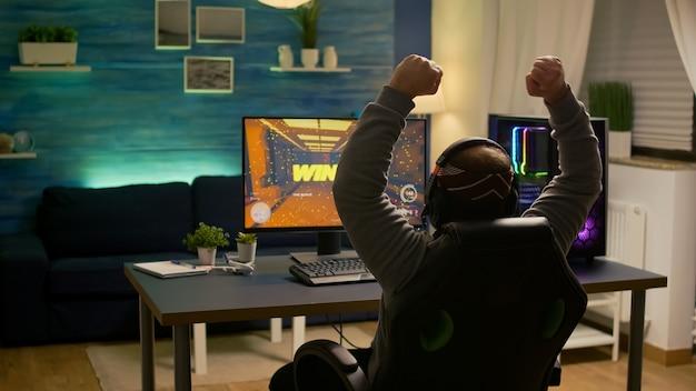 Videogiocatore che alza la mano dopo aver vinto la competizione sparatutto in prima persona indossando hradphone. giocatore professionista professionista che gioca ai videogiochi online con una nuova grafica su un computer potente
