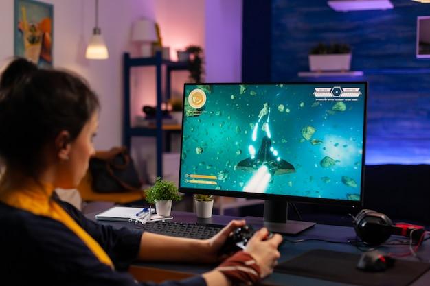 Видеогеймер играет в графическом киберпространстве, сидя на игровом кресле с помощью беспроводной консоли. женщина транслирует онлайн-игры для развлечения, используя клавиатуру rgb и джойстик для онлайн-чемпионата