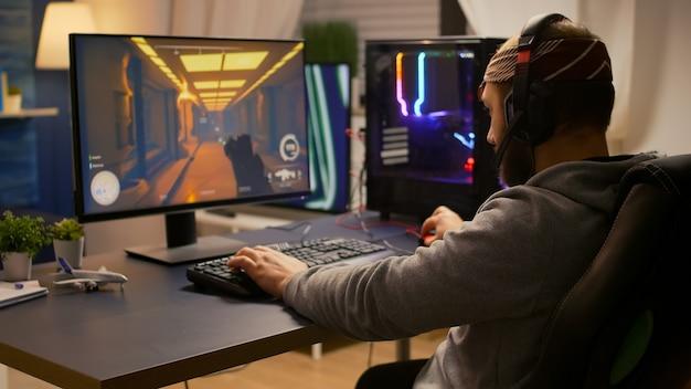 Videogiocatore che vince un torneo di sparatutto in prima persona utilizzando tastiera rgb e cuffie professionali. giocatore professionista che parla con altri giocatori online per gare di gioco su un computer potente