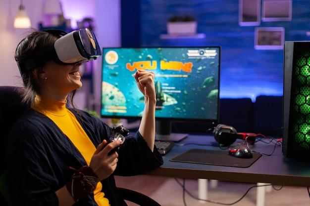 ビデオゲーマーの女性は、最新のジョイパッドでゲームをプレイするバーチャルリアリティゴーグルを使用してスペースシューティングゲームに勝ちます。強力なコンピューターで新しいグラフィックスを使用してオンラインビデオゲームをストリーミングするプロのゲーマー
