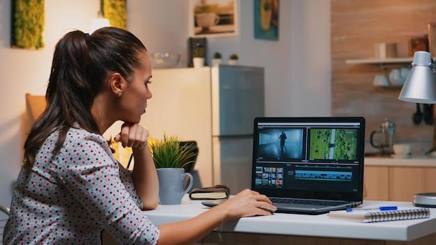 真夜中にモダンなキッチンの机の上に座っているプロのラップトップで自宅から編集する映像作家。オーディオフィルムモンタージュを処理する新しいプロジェクトで夜に働くクリエイティブなビデオエディタ。