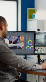 Videographer edits video project and cuts footage and sound using post production software and two m...