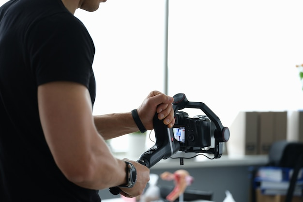 Videographer holds stabilizer with camera in hands closeup