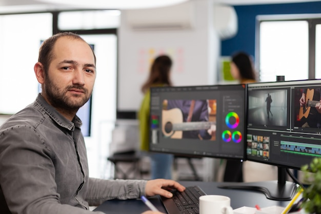 Videographer looking at camera smiling working in creative startup workplace using editing post production software on professional pc with two monitors processing video film montage
