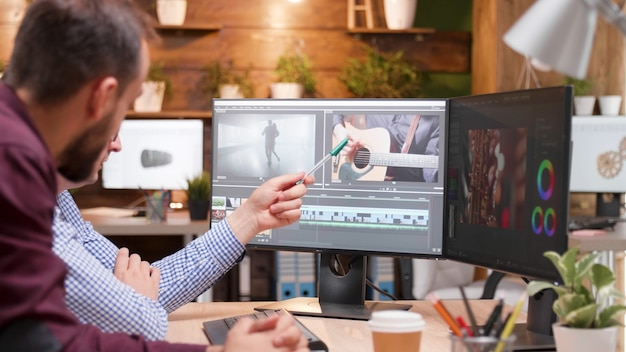 Videographer producer editing film production discussing movie graphic with photographer collegue working in creativity startup company. focused editor man developing digital footage. digital industry