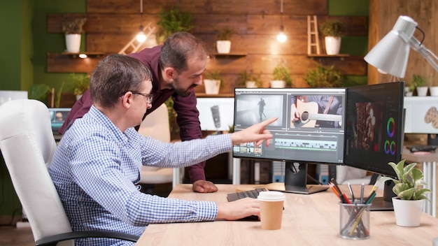Videographer producer editing film production discussing movie graphic with photographer