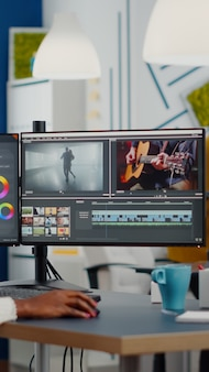 크리에이티브 스타트 업 에이전시 사무실에서 일하는 포스트 프로덕션 소프트웨어를 사용하여 헤드셋 편집 영화를 제작하는 비디오 그래퍼
